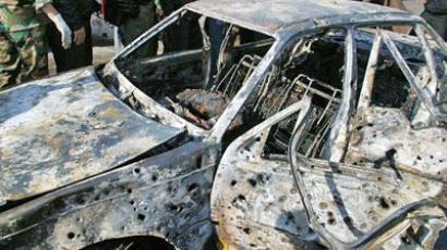 Syria, Damascus: A handout picture from the official Syrian News Agency shows a charred body inside a burnt car at the site of suicide attacks in a security service base in Damascus on December 23, 2011. (AFP Photo / Syrian TV)
