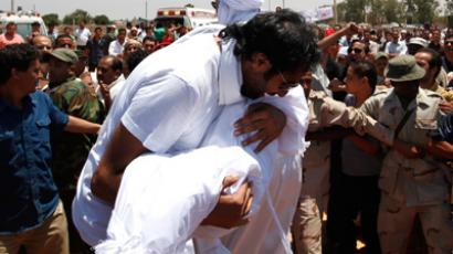 Khaled Al Khawaildi Al Hamadi cries as he carries the body of his son, who, according to the Libyan government, was killed by NATO air strikes (Reuters / Ahmed Jadallah)