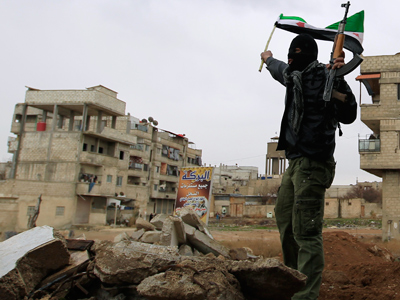 A Syrian soldier, who has defected to join the Free Syrian Army, holds up his rifle and waves a Syrian independence flag in Saqba, in Damascus suburbs, January 27, 2012 (Reuters / Ahmed Jadallah)