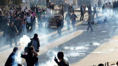 Anti-government protesters cover their faces from tear gas being fired in Adlb December 30, 2011 (Reuters / Handout)