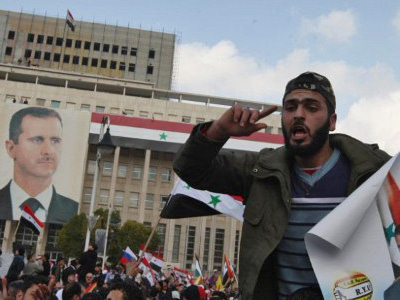 Damascus: A Syrian government supporter holds a portrait of President Bashar al-Assad during a pro-regime rally in Damascus on January 26, 2012 (AFP Photo/Louai Beshara)