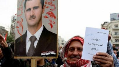 A man holding a picture of President Bashar al-Assad and a copy of the draft proposed constitution (AFP Photo / Anwar Amro)