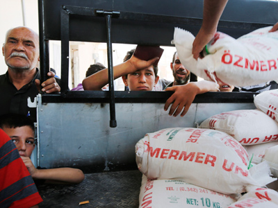 Civilians wait to receive food rations in the Bab Al-Salam refugee camp in Azaz (Reuters / Youssef Boudlal)