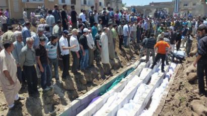 "A handout picture released by the Syrian opposition's Shaam News Network shows people watching the mass burial on May 26, 2012 of more than 100 victims killed in the central Syrian city of Houla in a massacre condemned by world leaders and described on May 28 by visiting UN-Arab League envoy Kofi Annan as ""an appalling moment with profound consequences."" (AFP Photo/HO/Shaam News Network)"