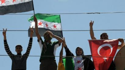 Syrian refugees wave Turkish and Free Syrian flags at the Yayladagi Refugee Camp in Antakya, on the Turkish-Syrian border, on April 10, 2012 (AFP Photo / Bulent Kilic)