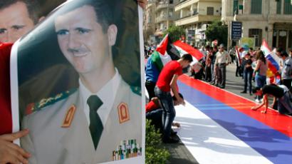 Supporters of Syrian President Bashar al-Assad's sign a large Russian flag during a rally at al-Sabaa Bahrat square in Damascus (Reuters / Khaled al-Hariri)