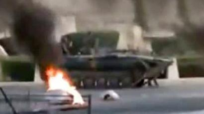 An image grab from a video uploaded on YouTube shows a Syrian army tank driving past burning tires in the city of Hama on July 31, 2011