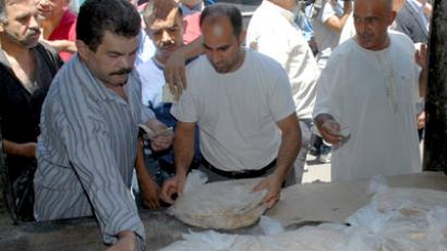 A handout picture released by the official Syrian Arab News Agency (SANA) on July 22, 2012, shows people from the al-Midan district of southern Damascus queuing to receive bags of bread being distributed, days after Syrian government forces purportedly ousted rebel forces from the district. (AFP Photo/SANA)