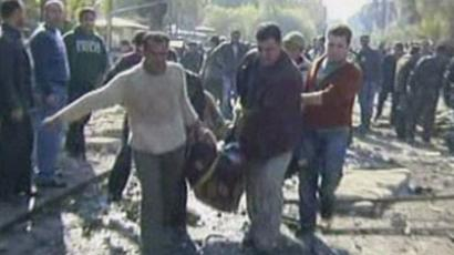 An image grab taken from Syrian state TV on December 23, 2011 shows Syrians carry away a dead body at the site of a suicide attack outside a security service base in Damascus on December 23, 2011 (AFP Photo)