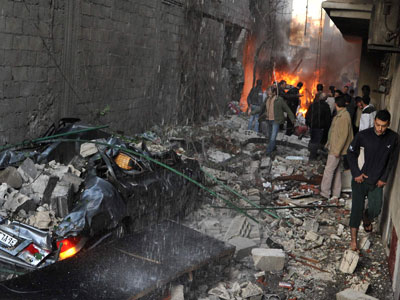 Syrian men inspect the scene of a car bomb explosion in Jaramana, a mainly Christian and Druze suburb of Damascus, on November 28, 2012. At least two car bombs exploded in Damascus killing and injureing a numbe of people.(AFP Photo / STR)