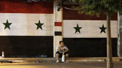 A Syrian man sits outside closed shops, their shutters painted with the colours of Syria's national flag, in the shopping district of the flashpoint city of Homs (AFP Photo / Jostph Eid)