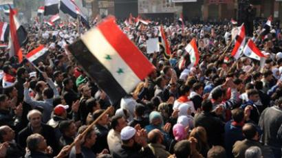 handout picture from the Syrian Arab News Agency (SANA) shows Syrians waving their national flag during a rally in support of the regime in the Damascus district of Daraya on December 1, 2011 (AFP Photo)