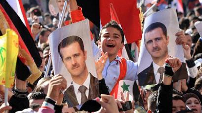 Syria, Damascus: Syrian government supporters hold pictures of President Bashar al-Assad during a pro-regime rally in Damascus on February 5, 2012. (AFP Photo/Louai Beshara)