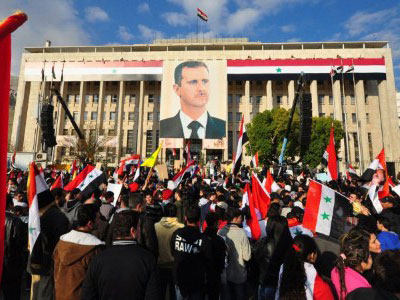 A poster of Syrian President Bashar al-Assad hanging from a building as pro-government protesters gather for a demonstration (AFP Photo / Sana)