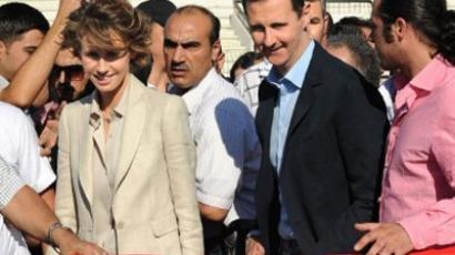 Syrian President Bashar al-Assad (R) and First Lady Asma al-Assad arrive at Al-Jalaa Stadium in Damascus (AFP Photo / Str)