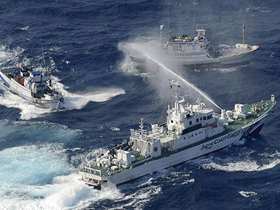 A Japan Coast Guard vessel (lower) sprays water against Taiwanese fishing boats, in the East China Sea near the Senkaku islands as known in Japanese or Diaoyu Islands in Chinese on September 25, 2012. (AFP Photo / Yomiuri Shimbun)