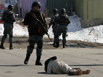 A wounded protester lies on the ground as Afghan policemen keep watch during a protest in Kabul February 23, 2012 (Reuters / Omar Sobhani)