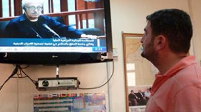 "An Iraqi journalist watches a live broadcast on state television showing Iraq's former deputy premier Tareq Aziz sitting in the dock as the supreme criminal court passes a verdict of ""deliberate murder and crimes against humanity,"" and sentencing him to death, on October 16, 2010 (AFP Photo / Ahmad Al-Rubaye)"