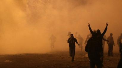 Cairo: Protesters run away from tear gas as they clash with riot police along a road which leads to the Interior Ministry, near Tahrir Square, in Cairo on November 22, 2011. (AFP Photo / Mahmud Hams)