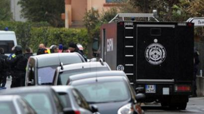 Members of GIPN van (French National Police Intervention Group), and firefighters stand near the Belle Paule residence, as members of the RAID special police forces unit are still laying siege to the apartment block where Mohamed Merah, the man suspected of a series of deadly shootings, was holed up, on March 22, 2012 in Toulouse, southwestern France (AFP Photo / Philippe Desmazes)