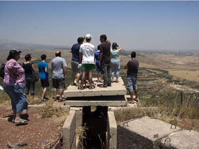 Israelis look from an Israeli army post near the village of Buqaata in the Golan Heights at the nearby Syrian village of Jebata al-Khashab (AFP Photo / Menahem Kahana)