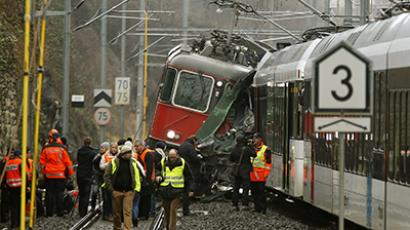 Swiss rescue personnel and journalists stand in front of a demolished RE 440 train after a train crash in the northern Swiss town of Neuhausen am Rheinfall January 10, 2013. (Reuters / Arnd Wiegmann)