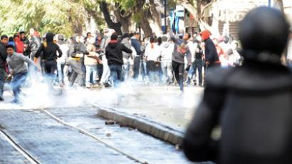 Tunisian protesters run away after police fired tear gas during a demonstration following the funeral of assassinated opposition leader Chokri Belaid on Habib Bourguiba Avenue in central Tunis on February 8, 2013. (AFP Photo/Salah Habibi)