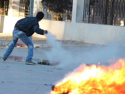 A protester throws a tear gas canister back at police during clashes in Siliana November 28, 2012 (Reuters / Stringer)