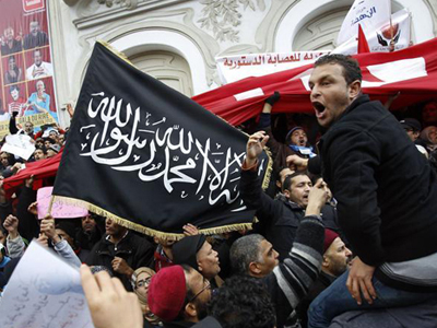 Protesters shout slogans and wave flags during a demonstration in support of the ruling party Ennahda in Tunis February 9, 2013. (Reuters /  Zoubeir Souissi )
