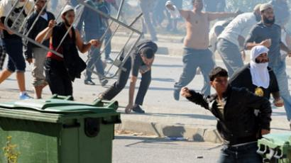 Tunisian protesters throw stones during a protest against a film mocking Islam outside the US embassy in Tunis on September 14, 2012. (AFP Photo/Fethi Belaid)