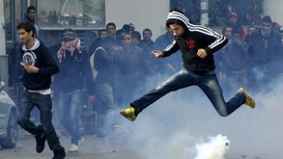 A Tunisian protester jumps amid smoke after police fired tear gas during a rallye outside the Interior ministry to protest after Tunisian opposition leader and outspoken government critic Chokri Belaid was shot dead with three bullets fired from close range, on February 6, 2013 in Tunis (AFP Photo / Fethi Belaid)