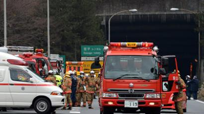 Rescue workers and policeman gather alongside emergency services vehicles on the road leading to the entrance of the collapsed Sasago tunnel on the Chuo expressway in Koshu city, Yamanashi prefecture, some 80-kilometres west of Tokyo on December 2, 2012. (AFP Photo / Yoshikazu Tsuno)