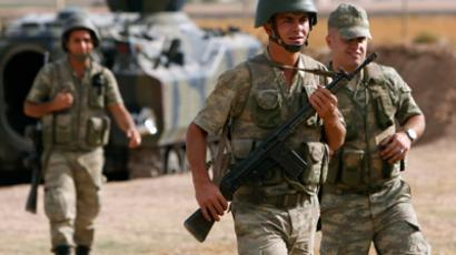 Turkish soldiers walk as they stand guard on the Turkish-Syrian border near the Akcakale border crossing, southern Sanliurfa province, October 5, 2012 (Reuters)