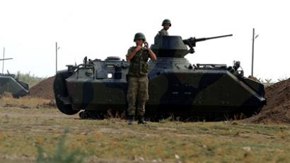 A Turkish army armoured personnel carrier is dug in on the border with Syria near Akcakale on October 7, 2012 (AFP Photo)