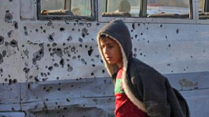 Baghdad : A boy walks past by a bus damaged from shrapnel after a booby-trapped motorcycle exploded near a group of day labourers waiting to pick up work, on January 5, 2012 in the Shiite district of Sadr City, north of Baghdad. (AFP Photo/Ahmad Al-Rubaye)