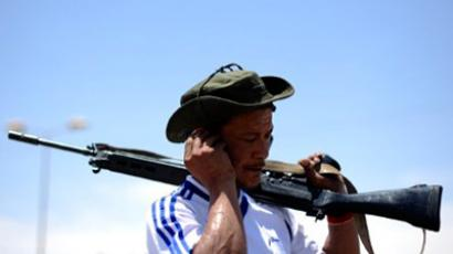 Libyan rebel speaks on a mobile phone as he stands guard on a checkpoint the outskirts of eastern rebel-held city of Ajdabiya on May 17, 2011 (AFP Photo / Saeed Khan)