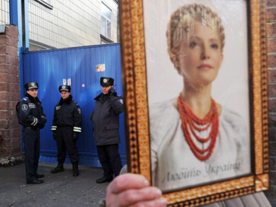 A Ukrainian supporter of Yulia Tymoshenko holds her portrait during rally in front of the Kiev 's prison as they mark her 51st birthday on November 27, 2011 (AFP Photo / Sergey Supinsky)