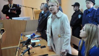 Yevgenia Karr (R) holds hands with her mother Yulia Tymoshenko who addresses Ukrainians while Rodion Kireyev, judge of Kiev Pechersky court reads a verdict to her during the sittings in Kiev on October 11, 2011. (AFP Photo/ Sergei Supinsky)
