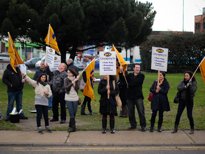 PCS (Public and Commercial Services) union members wave flags at cars near Heathrow Airport, west of London, on November 30, 2011 (AFP Photo / Carl Court)