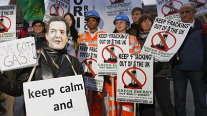 Demonstrators, including one wearing a mask of British Chancellor of the Exchequer George Osborne (L) pose placards in protest against hydraulic fracturing for shale gas outside parliament in London on December 1, 2012.  (AFP Photo / Justin Tallis)