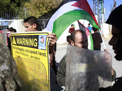 Palestinian demonstrators hold banners and wave their national flag during a weekly protest against Israel's controversial separation barrier in the West Bank village of Maasarah, near Bethlehem, on November 30, 2012. (AFP Photo/Musa Al-Shaer)