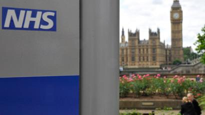 A National Health Service (NHS) sign is seen in the grounds of St Thomas' Hospital, in front of the Houses of Parliament in London (Reuters / Toby Melville)