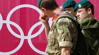 Marines pass the Olympic rings outside the London 2012 Olympic Park at Stratford in London July 12, 2012 (Reuters/Luke MacGregor)