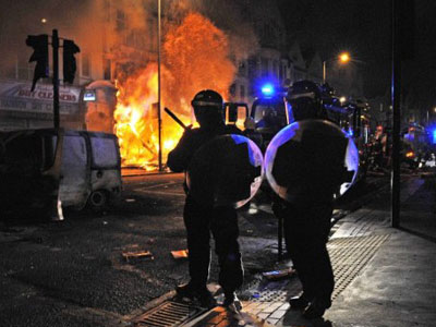 British riot policemen stand guard in front of a burning building in Croydon, South London (AFP Photo / Carl de Souza)