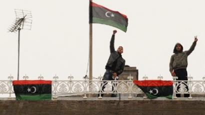 Anti-Kadhafi regime protesters gesture as the Libyan flag of the former monarchy flies on the roof of the Libyan embassy in central London, on March 16, 2011 (AFP Photo / Ben Stansall)
