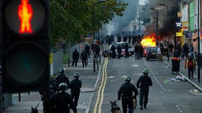 London: Riot police tackle a mob after a number of cars are set alight in Hackney, north London on August 8, 2011 (AFP Photo/Leon Neal)