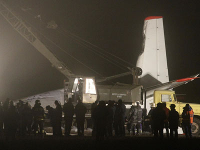 A worker operates a crane near the damaged Antonov 24 turboprop plane near the airport in Donetsk, February 13, 2013.(Reuters / Stringer)
