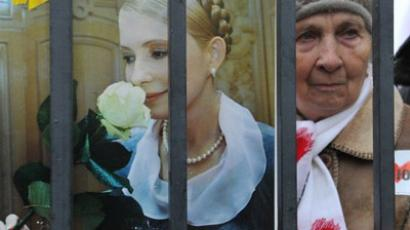 A supporter of Ukraine's former Prime Minister Yulia Tymoshenko holds a picture of the opposition leader during a mass rally in front of Ukrainian court in Kiev on December 13, 2011. (AFP Photo / Sergei Supinsky)
