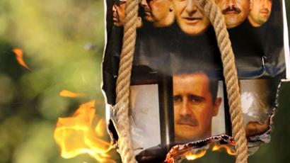 Cyprus, Nicosia : A makeshift gallows with a poster shows the pictures of former Syrian president Hafez al-Assd (top-C), his sons current President Bashar al-Assad (2nd L and bottom C) and Maher (L), their brother in-law General Assef Shawkat (2nd R) and businessman Rami Makhluf (R), during an anti-regime protest outside the Syrian embassy in the Cypriot capital Nicosia on July 31, 2011. (AFP Photo  / Patrick Baz)