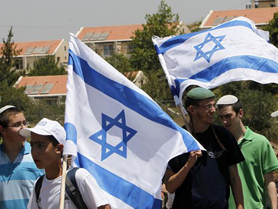 Jewish settlers hold Israeli flags near the West Bank city. (Reuters / Ronen Zvulun)